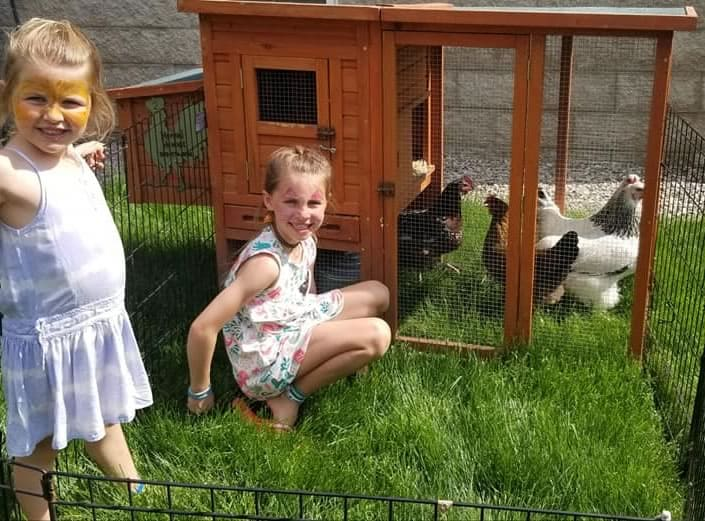 Young girls with chicken rental and coop